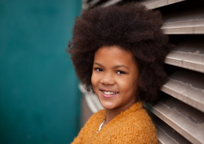 Clare J Sheridan Photography - Smiling girl in orange cardigan