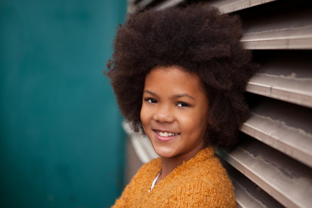 Clare J Sheridan Photography - Smiling girl in orange cardigan