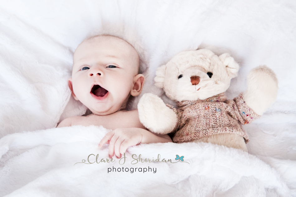Yawning baby with teddy