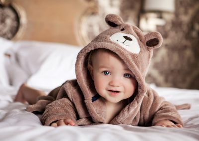 Clare J Sheridan Photography - A baby boy in Teddy Bear dressing gown laid on a bed