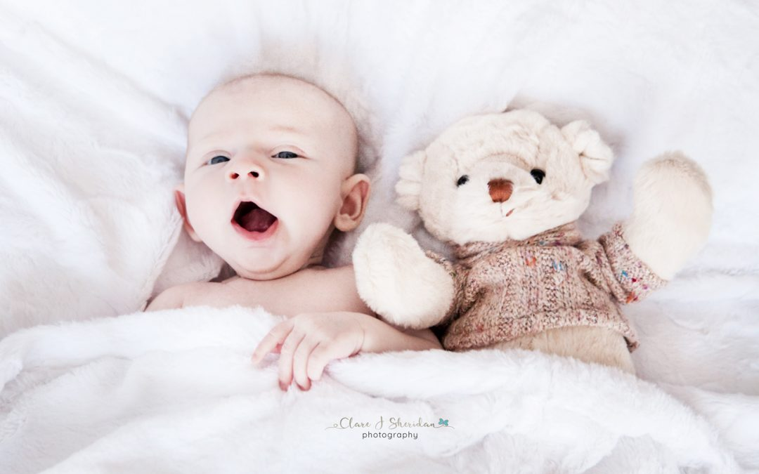 Baby girl yawning next to Teddy bear in bed - Clare J Sheridan Photography